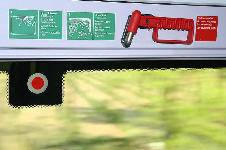 An emergency hammer near the window of a vehicle