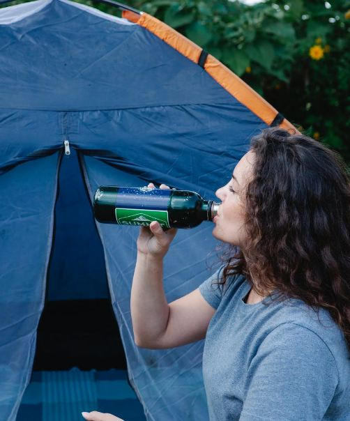 Hiker Drinking Beverage Against Tent in Campsite