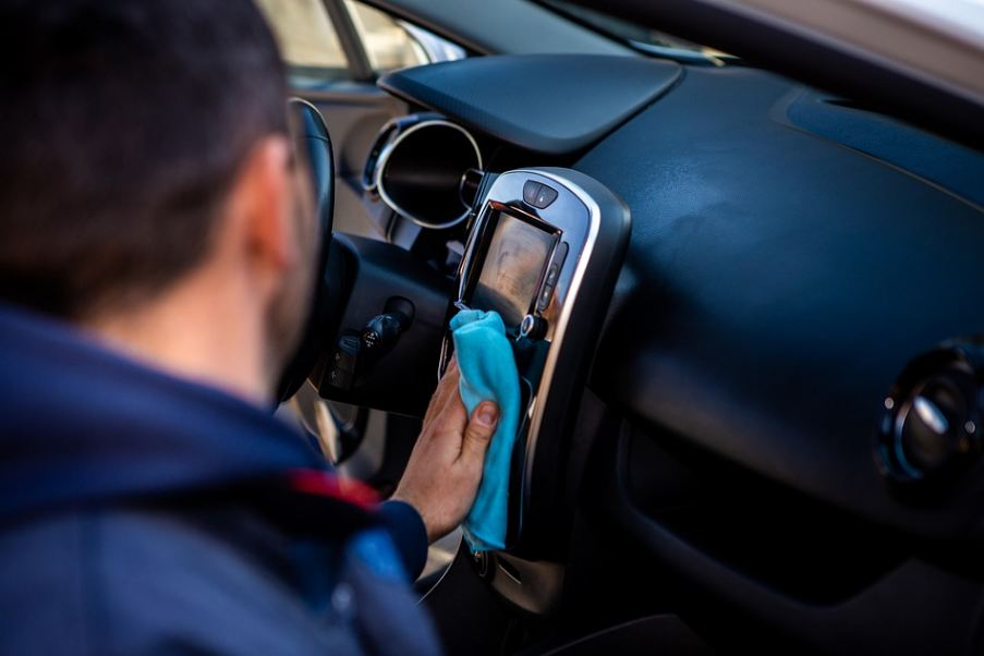 man cleaning the interior of his car