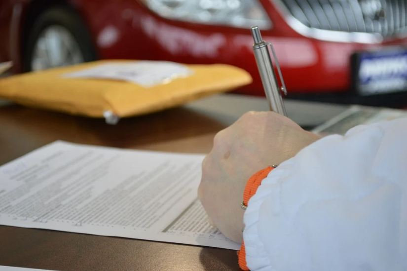 signing a contract, yellow folder, red car at the back
